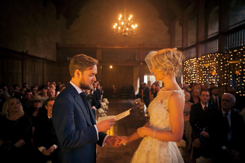 Groom reads vows to bride, warm orange glow, in Achnagairn Castle, Scotland