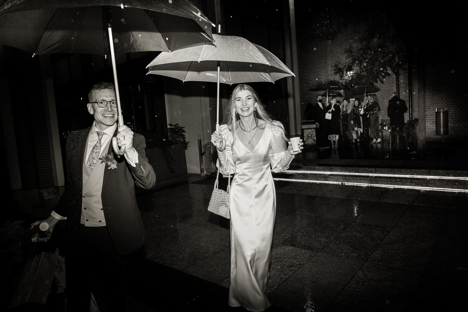 Bride and groom leave Fitzrovia Chapel with an umbrella in the rain