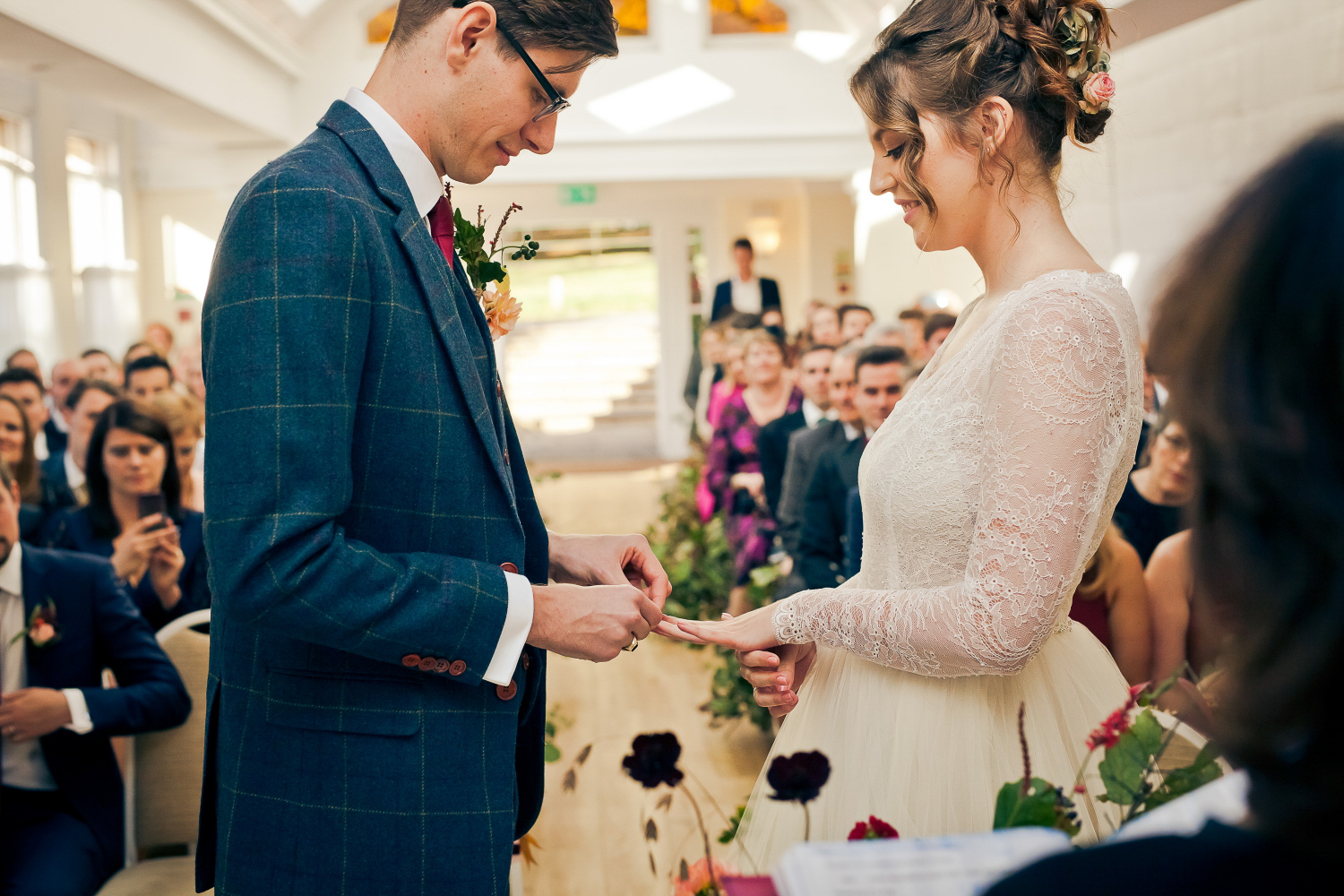 Groom puts the wedding ring on his bride's finger in the Belvedere Room at Pembroke Lodge