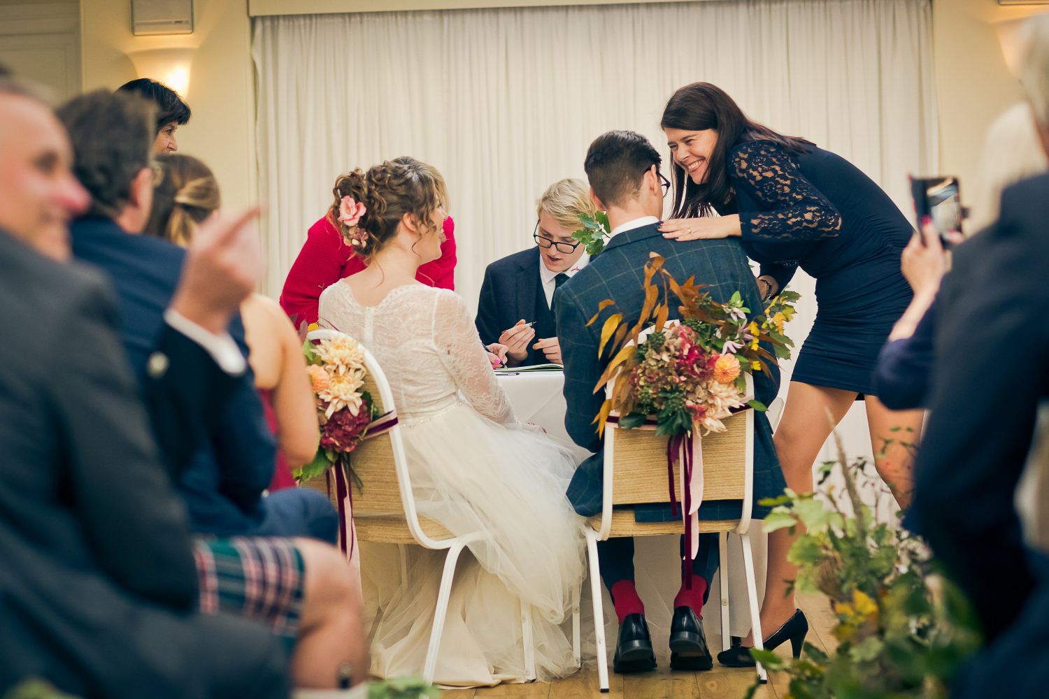 A guest congratulates the groom, laughing and overjoyed