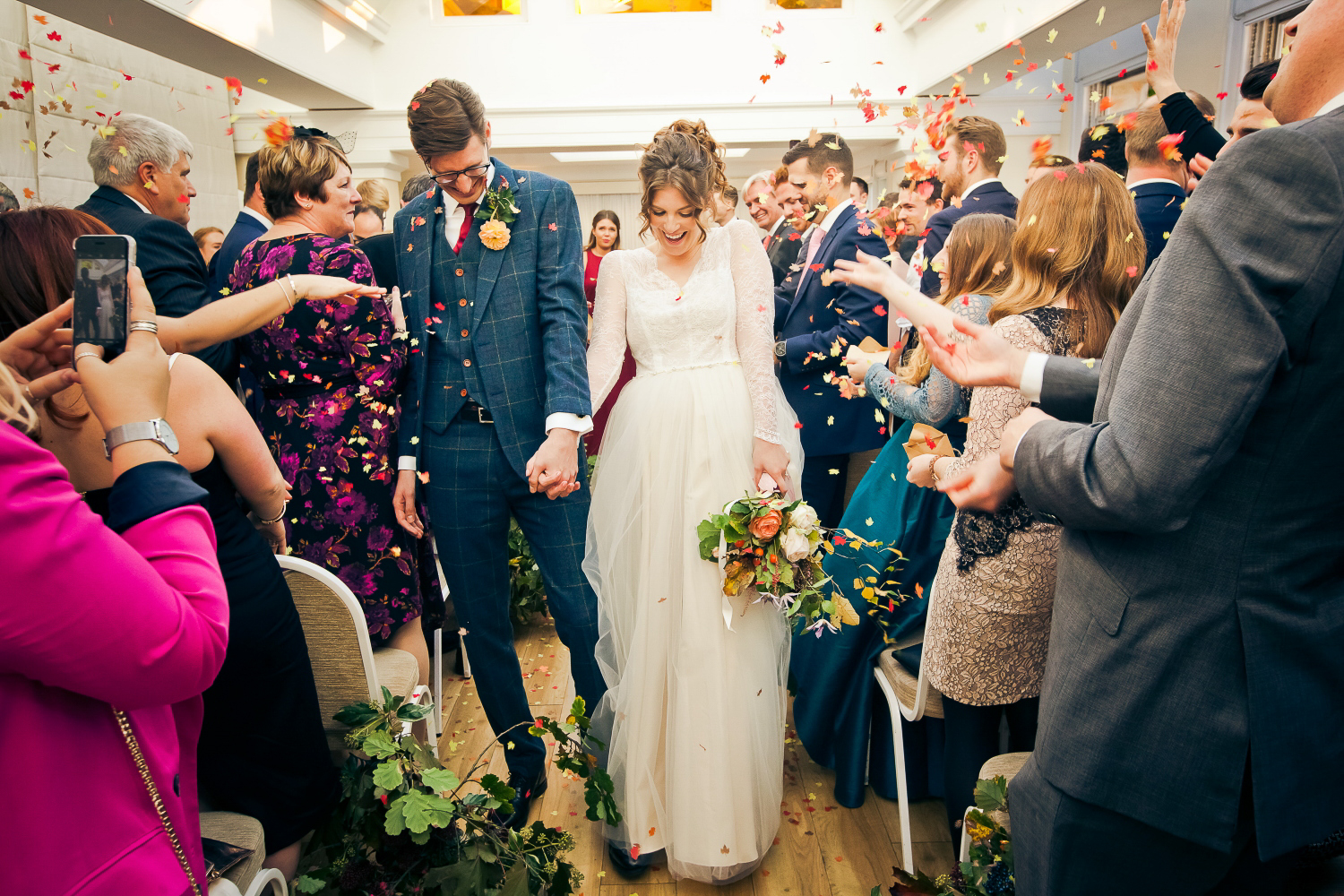 As the bride and groom walk up the aisle, confetti, hands and love fly through the room