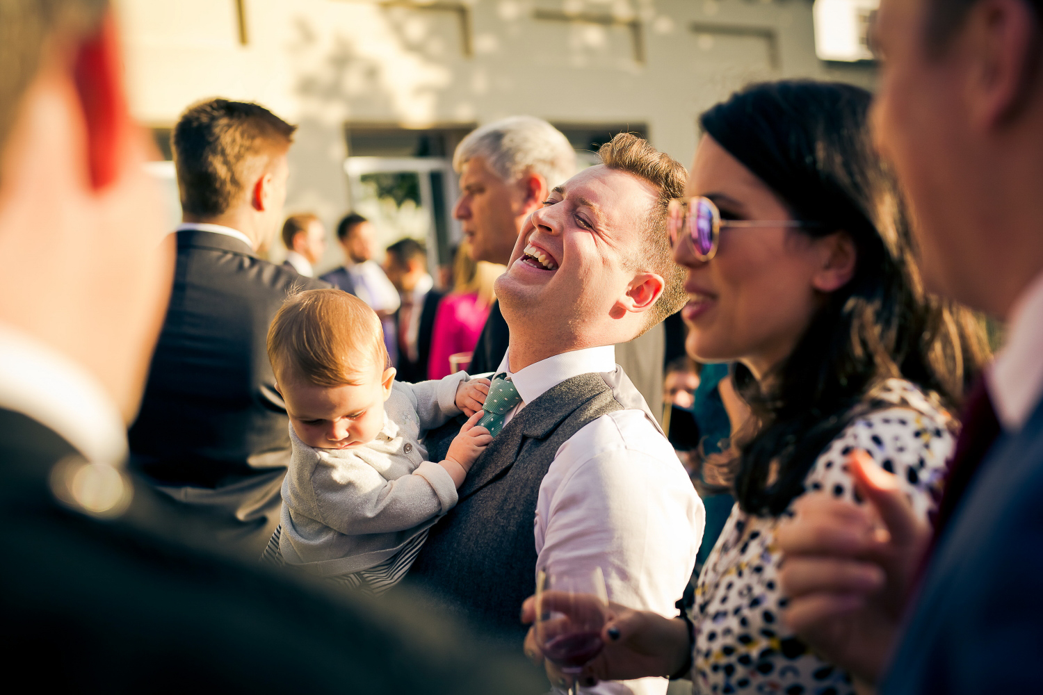 Guest laughing at a wedding holding a baby