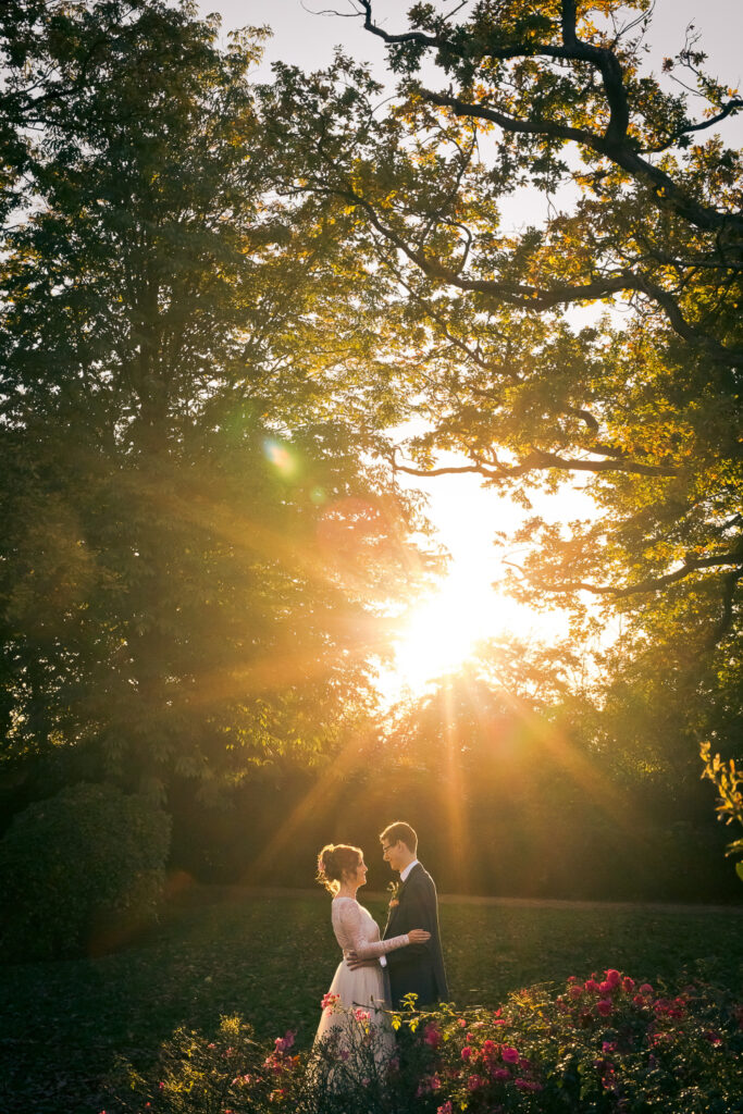 A delightful picture of a bride and groom in an English rural setting under trees