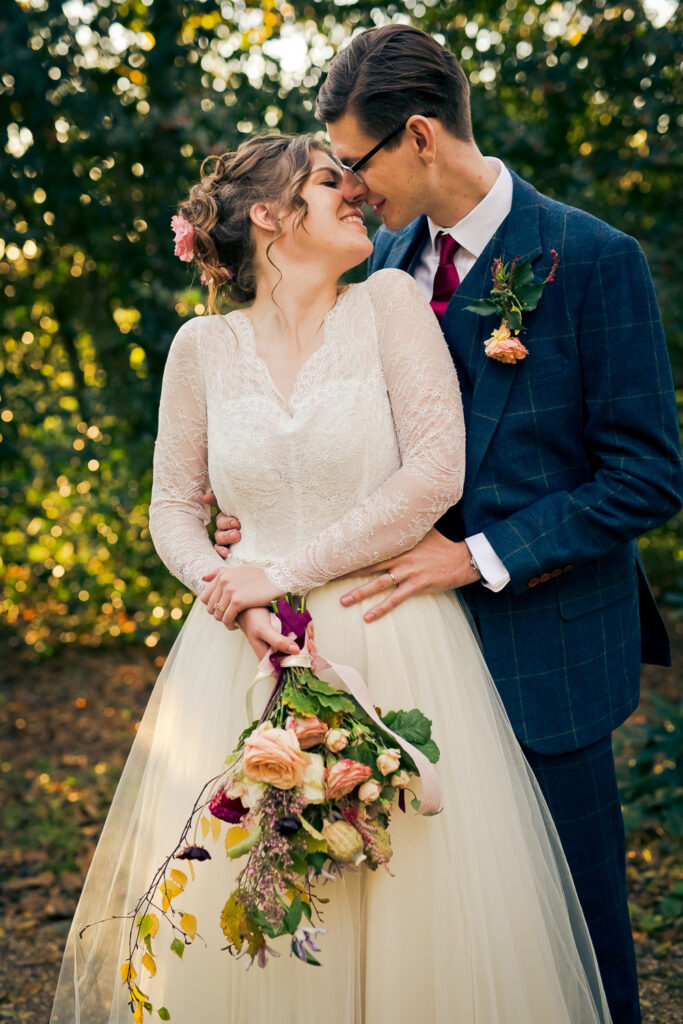 A gorgeous picture of a bride and groom with autumnal flowers and colours