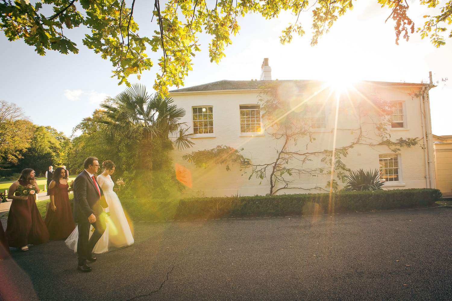 A sunny walk under the trees, in front of the wedding venue with the bride's dad and bridesmaids