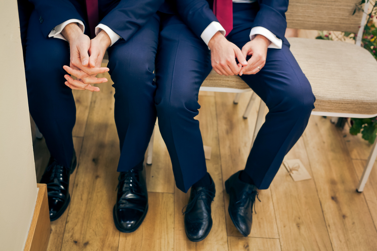 Two men are sat, resting on their knees, during an emotional wedding ceremony