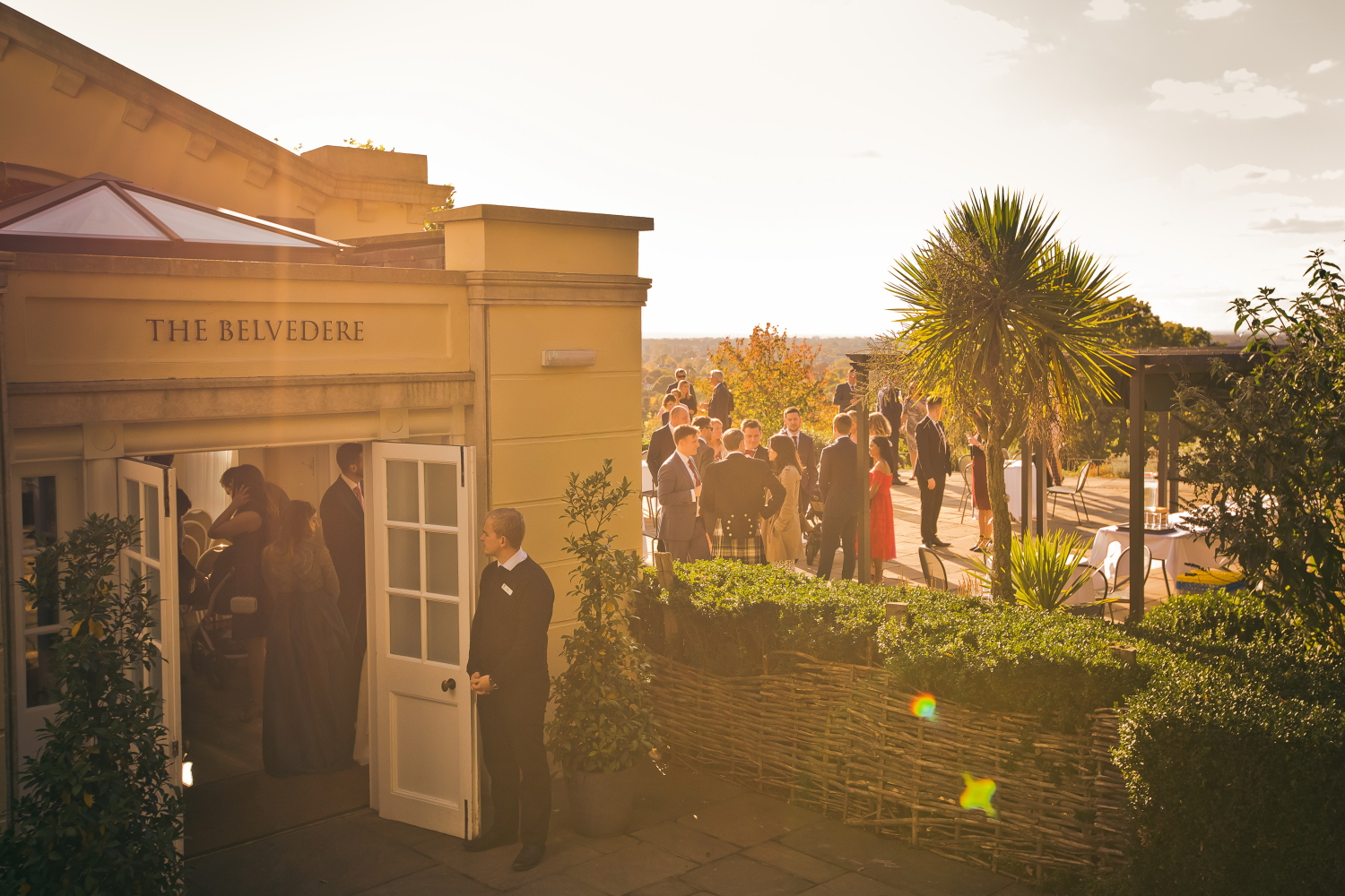 A warm, sunny scene outside the Belvedere Room, as guest mingle and drink on the terrace in the sunshine