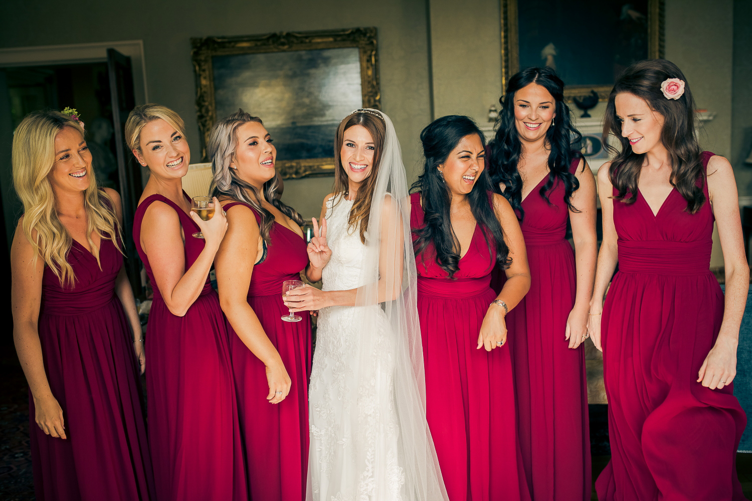 Bride and bridesmaids laugh during photo in Falconhurst wedding venue